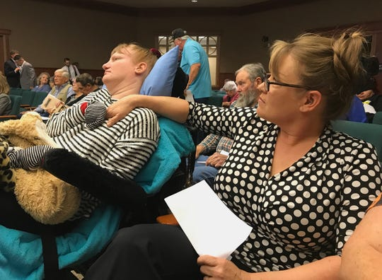 Shingletown resident Shelly White comforts her daughter, Malinda, at the special California Public Utilities Commission meeting in Redding on Thursday, Oct. 24, 2019. White described how the PG&E outages have put her medically-fragile daughter at risk.