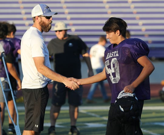 Shasta High School head football coach J.C. Hunsaker shakes hands with one of his varsity players following their practice on Wednesday, Oct. 23, 2019, in advance of Friday's River Bowl.