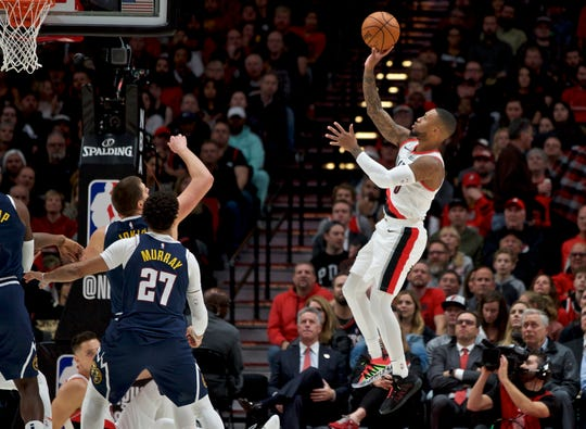 Portland Trail Blazers guard Damian Lillard, right, shoots over Denver Nuggets guard Jamal Murray during the first half of an NBA basketball game in Portland, Ore., Wednesday, Oct. 23, 2019.