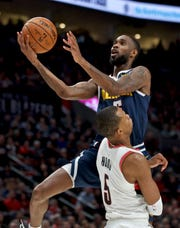 Denver Nuggets guard Will Barton goes to the basket over Portland Trail Blazers guard Rodney Hood (5) during the first half of an NBA basketball game in Portland, Ore., Wednesday, Oct. 23, 2019.