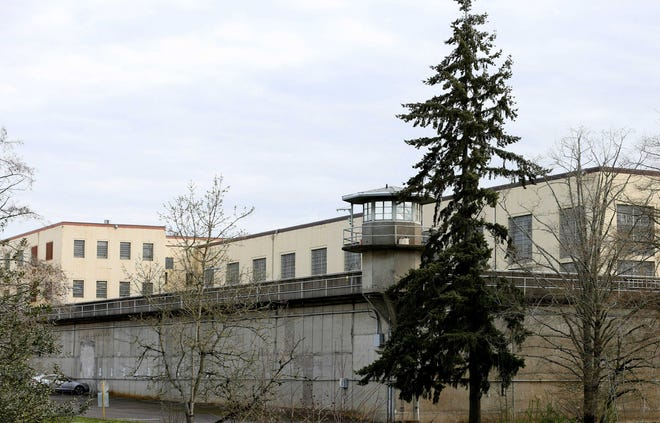Tall concrete walls with guard towers surround the Oregon State Penitentiary.