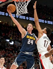 Denver Nuggets forward Mason Plumlee, left, shoots next to Portland Trail Blazers forward Skal Labissiere during the first half of an NBA basketball game in Portland, Ore., Wednesday, Oct. 23, 2019.