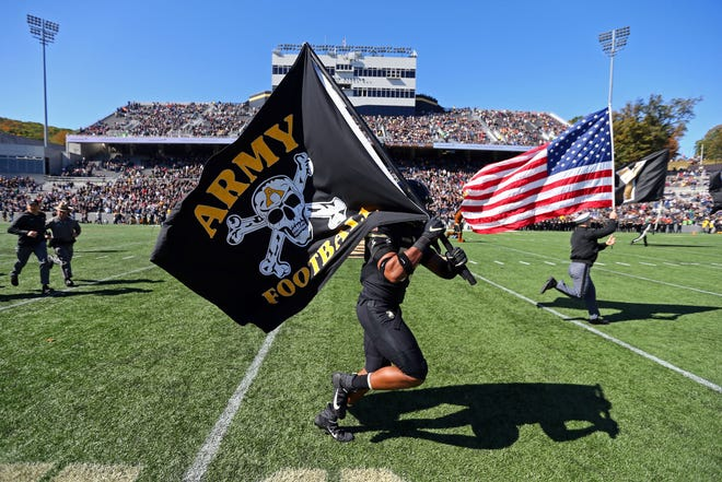 The Army Black Knights take the field with flags before a game against the Tulane Green Wave at Michie Stadium.