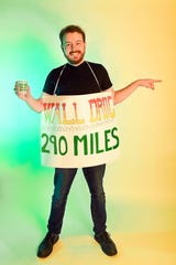 Argus Leader reporter Trevor Mitchell creates a handmade Halloween costume of one of many Wall Drug billboards that can be seen along Interstate 90.