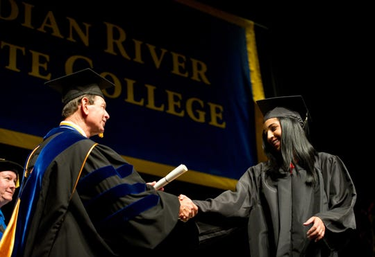 Angelique Cannestro (right) smiles as she receives her adult high school competency-based diploma from Indian River State College President Edwin Massey during the Adult Secondary Education Graduation Ceremony at the McAlpin FIne Arts Center on May 15, 2012. The school is in the initial stages of its search for a new president.