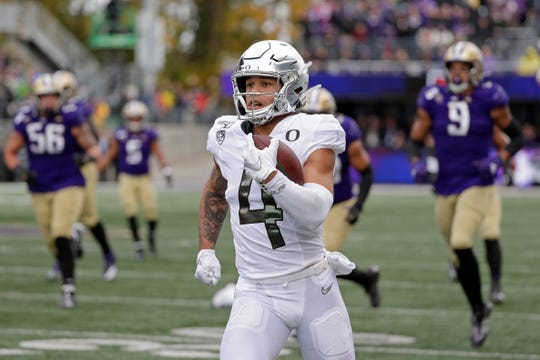 Mycah Pittman, a Calabasas High graduate, leaves Washington defenders behind as he runs after a pass reception for a 36-yard touchdown in the second half of Oregon's 35-31 win last Saturday in Seattle.