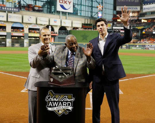 Brewers star Christian Yelich, right, a Westlake High graduate, acknowledges the crowd while being presented with the National League's Hank Aaron Award by Aaron himself, center, and Joe Torre, left, before Game 2 of the World Series in Houston on Wednesday.