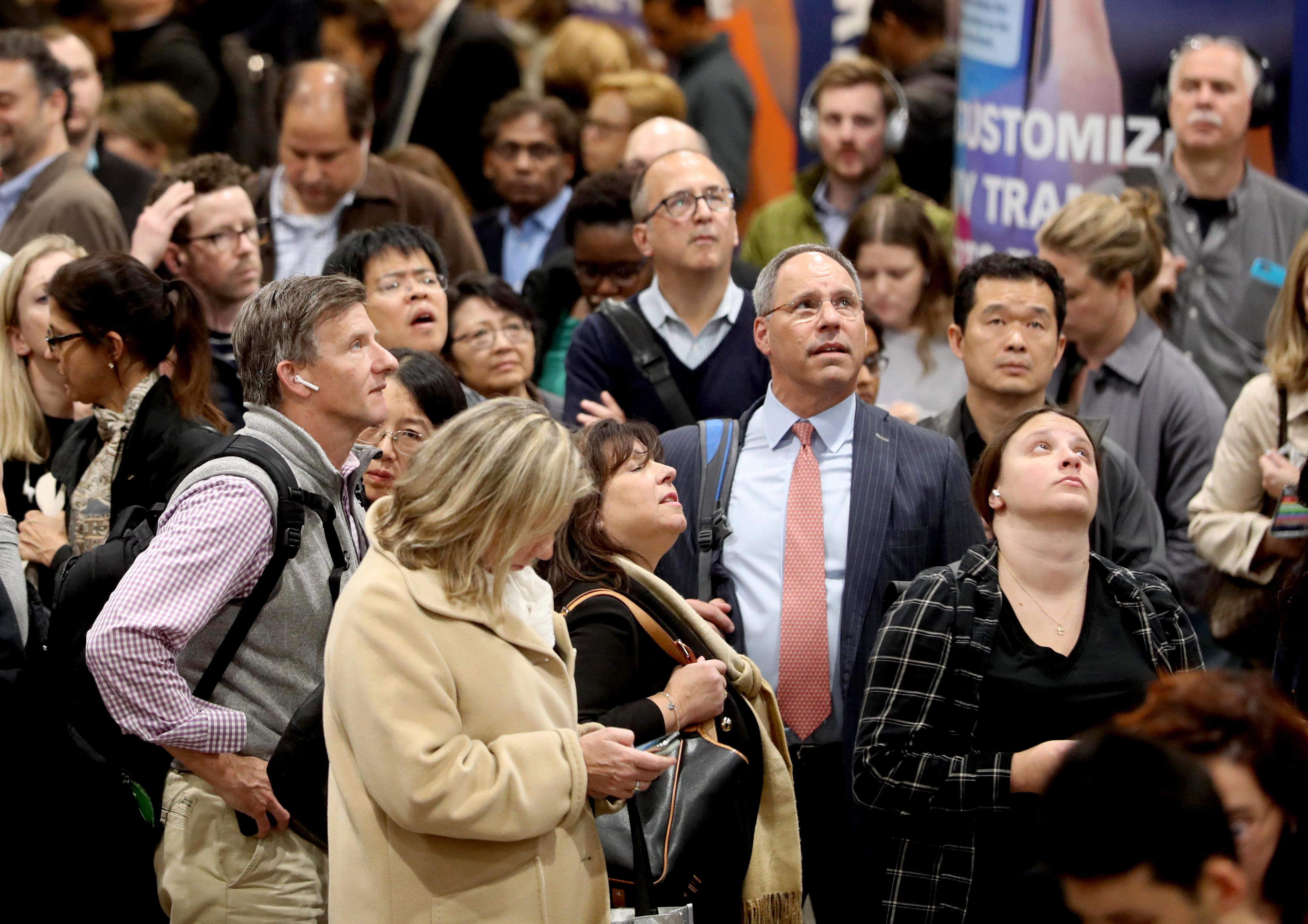 Commuters crowd under train schedule boards in Penn Station waiting to find out what track their homebound train would be departing from during the evening commute Oct. 23, 2019. Once track locations appear on the boards, commuters rush to their gates, with sometimes only minutes to spare before their train leaves the station.