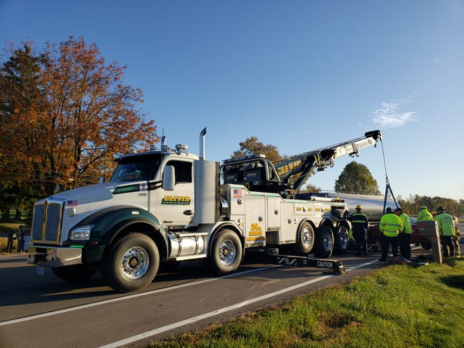 Clever Towing uses a crane to remove a small sedan from underneath a tanker truck following a crash Thursday morning that claimed the life of a local man.