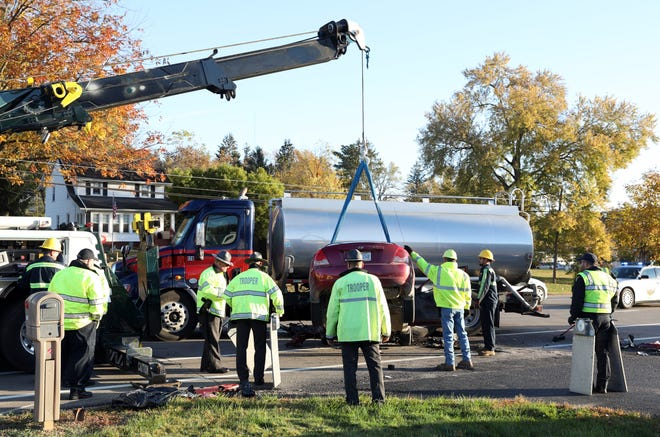 Workers from Clever's Towing had to lift a car to remove it from under a tanker truck after a fatal wreck on US 40 West of Zanesville on Thursday.