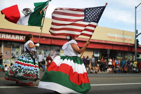 Performers carry the Mexican and U.S. flags in a parade in Santa Ana, California, in September 2019.