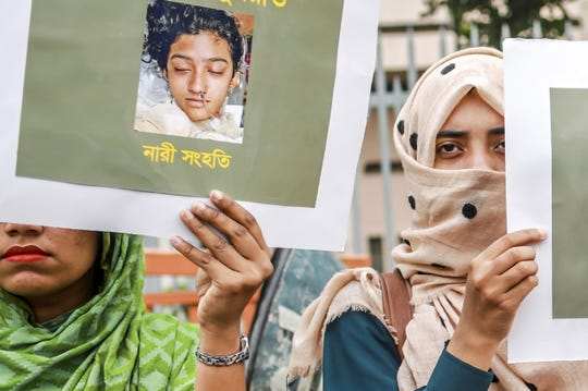 In this file photo taken on April 12, 2019 women hold placards with a photograph of schoolgirl Nusrat Jahan Rafi at a protest in Dhaka, following her murder by being set on fire after she had reported a sexual assault.