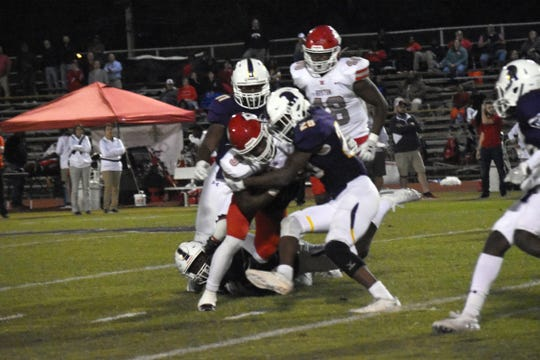 Alexandria Senior High's Jermaine McNeal (29) and Marquis Dangerfield stop Ruston's Ketravion Hargrove last season.