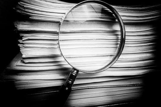 Handheld Magnify glass inspects paper documents