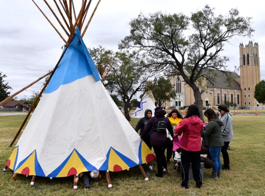 Jaxtyn Doggett, 5, pokes his head from beneath a Nez Percé-inspired tipi Friday at McMurry University's Tipi Village.