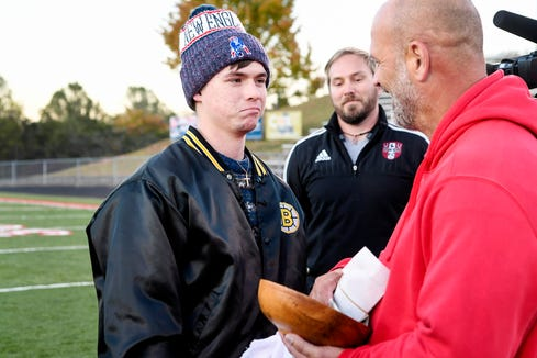 Devin Gildner is presented with a monetary gift from Erwin soccer coach Tate MacQueen on October 24, 2019. Gildner experienced a sudden onset of paraplegia after suffering a rare spinal cord injury called Surfer's Myelopathy. The teen was able to walk onto the field to flip the coin before Erwin's game and receive the gift.