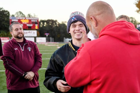 Devin Gildner laughs as Tate MacQueen, Erwin's soccer coach, wipes his eyes after presenting Gildner with a monetary gift October 24, 2019. Gildner experienced a sudden onset of paraplegia after a rare spinal cord injury called Surfer's Myelopathy. The teen was able to walk onto the field to flip the coin before Erwin's game.