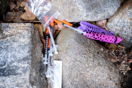 A collection of syringes among rocks behind the fence of a parking area on Walnut Street in downtown Asheville on Oct. 25, 2019.