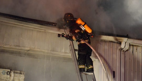 A firefighter searching the roof for more fire early Friday.