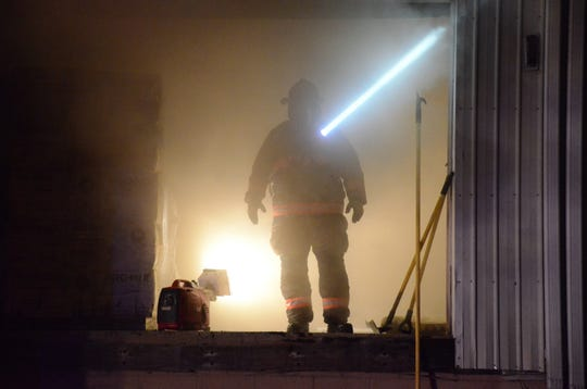 A firefighter with a flashlight in one of the open doorways of the burning building.