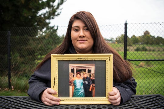 Ciera Woodard, 20, poses with a photograph of her grandfather Gary Woodard on Friday, Oct. 25, 2019 in Battle Creek, Mich. Gary, a Vietnam vet, passed away on Oct. 18, and Cierra's family has turned to crowdfunding to pay for funeral expenses.