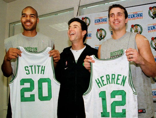Boston Celtics coach Rick Pitino shares a light moment with newly acquired players Bryant Stith, left, and Chris Herren in 2000.