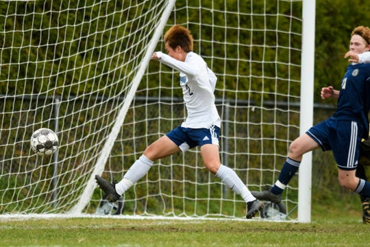MMU's Benjin Johnson (2) kicks the ball into the net for a goal during the boys soccer quarterfinal game between the Mount Mansfield Cougars and the Essex Hornets at Essex High School on Friday afternoon October 25, 2019 in Essex, Vermont.