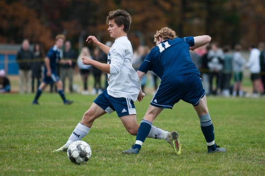 MMU's Will Hauf (7) plays the ball past Essex's Will Deziel (11) during the boys soccer quarterfinal game between the Mount Mansfield Cougars and the Essex Hornets at Essex High School on Friday afternoon October 25, 2019 in Essex, Vermont.
