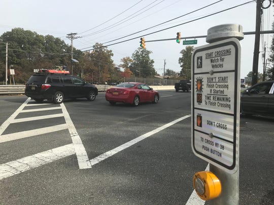 A roadside sign offers directions to pedestrians seeking to cross Route 38 at Chestnut Street in Cherry Hill.