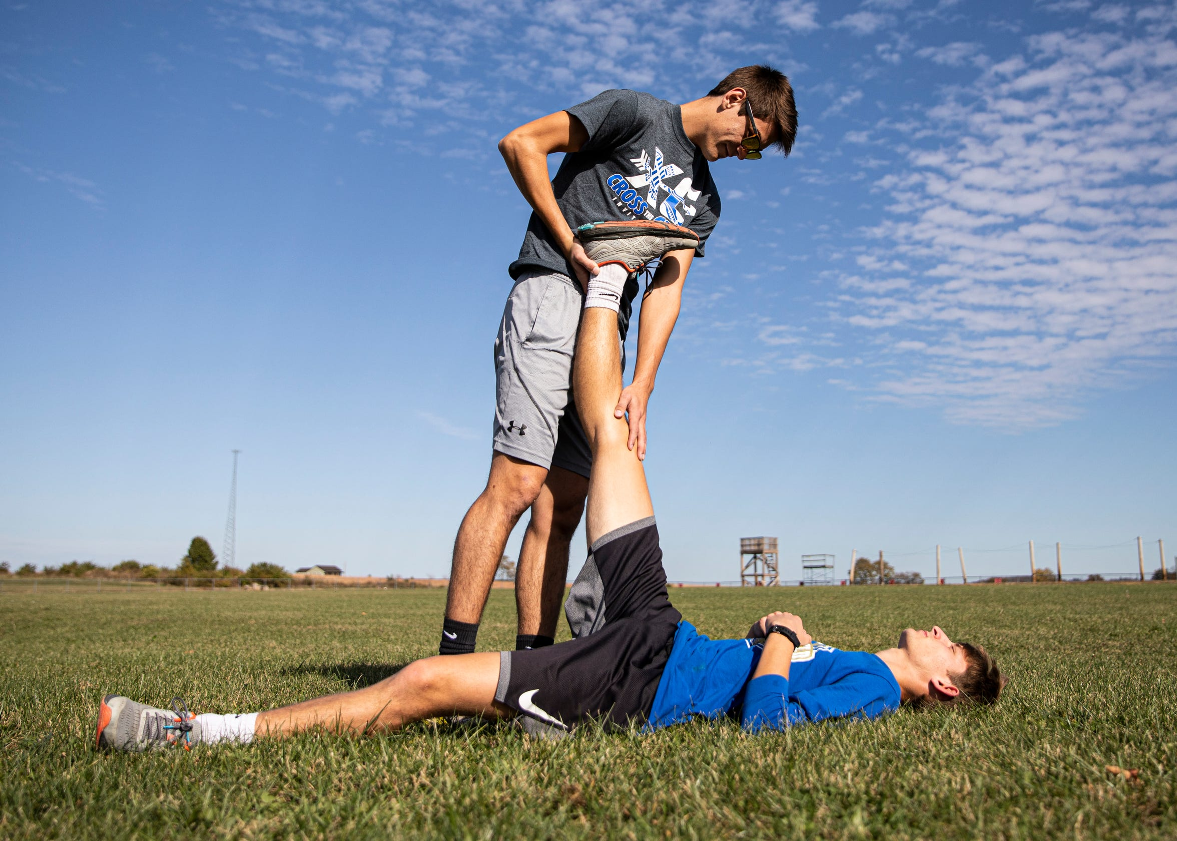 To help prevent injury and loosen the muscles, senior Emmitt Cunningham helps stretch out fellow cross country senior Noah Kanniard before Kanniard participates in a practice run after school in Frankfort, Ohio.