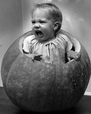 OCTOBER 28, 1973: Lisa Smith, daughter of Mr. and Mrs. Tom Smith, doesn't seem to be too pleased with the idea of celebrating Halloween in a pumpkin shell. Her father threw the 91-pound pumpkin in their backyard.