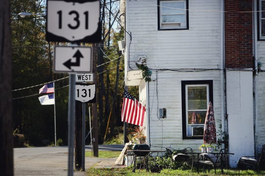 An American flag hangs from the front porch of an apartment building off of  Main Street/Ohio 131 in the small village of Newtonsville, Ohio.
