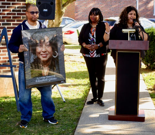 Principal Isabella Scocozza (right) and Vice Principal Gwendolyn Long outside Soehl Middle School in Linden at a dedication ceremony for a memorial sign honoring longtime school secretary Elizabeth Givens, who died in April. Givens' son Steven holds a photo of his mother made up of hundreds of small photos of Soehl students.
