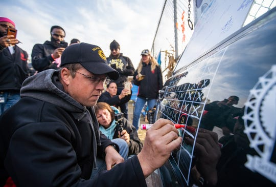 UAW Local 598 Alternate Committee Rep Bo Browning circles the date marking the last day of the UAW Strike against General Motors on a truck door outside of Flint Assembly symbolic to the door used in the Flint Sit-down Strike as members celebrate outside of Flint Assembly h after UAW ratified their contract with General Motors on Friday, October 25, 2019.