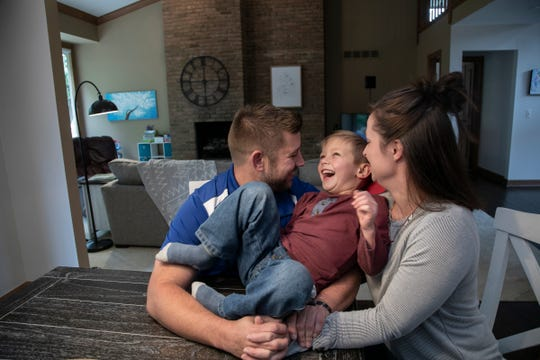 Andrew Smith, 35, plays with his son Jonathan Smith, 5, with his wife Sarah Smith, 33, at right in their new home in Rochester Hills on Oct. 4, 2019.