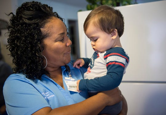 Terri Kirkpatrick, a social worker, holds Jorge Webster during a home visit provided by Strong Beginnings, which receives some funding through PNC Bank.
