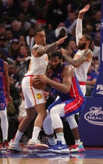 Andre Drummond is defended by Hawks' John Collins, left, and DeAndre' Bembry during the fourth quarter Thursday.