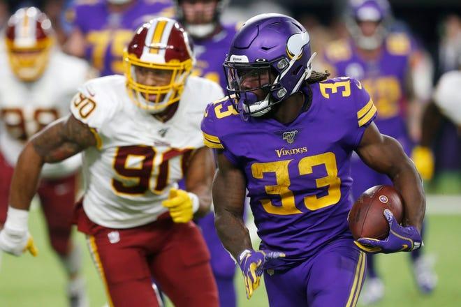 Vikings running back Dalvin Cook (33) runs from Washington linebacker Montez Sweat (90) during the second half on Thursday.
