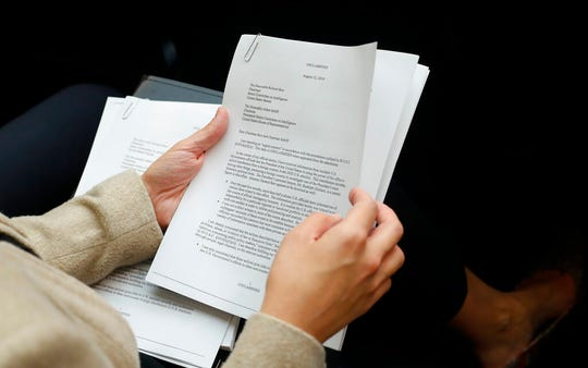A member of the audience holds a copy of the Whistle-Blower Complaint letter sent to Senate and House Intelligence Committees during testimony before the House Intelligence Committee on Capitol Hill.