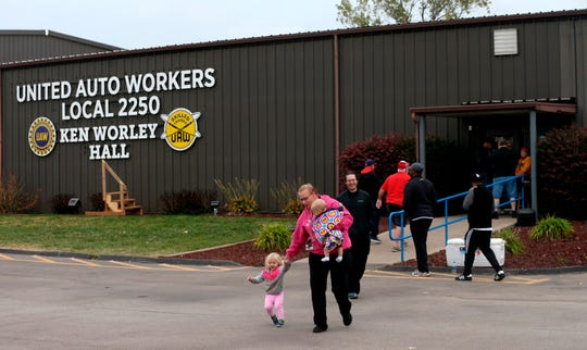 "United Auto Worker Lindsey Higgins, exits the the UAW Local 2250 Ken Worley Hall with her two children after voting on the offer in Wentzville, Mo. ""I don't feel great about the contract but I have these two to think about. I can't keep striking. I've got to keep a roof over their head,"" said Higgins."