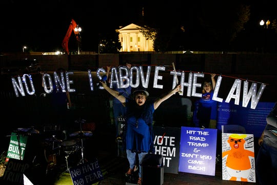 "Protesters with Kremlin Annex with a light sign that reads ""NO ONE IS ABOVE THE LAW"" call to impeach President Donald Trump in Lafayette Square Park in front of the White House in this Sept. 26, 2019, file photo."