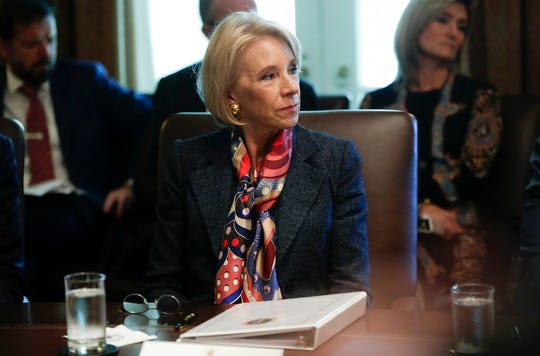 In this Oct. 21, 2019, photo, Education Secretary Betsy DeVos listens to President Donald Trump during a Cabinet meeting. A federal judge has held DeVos in contempt of court for violating an order to stop collecting loans from thousands of former for-profit college students.