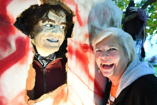 Jennifer Litomisky of Pleasant Ridge gives a vampire grin beside her homemade Jack Nicholson character from 'The Shining,' displayed in her front yard.