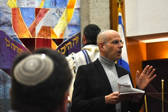 Rabbi Aaron Bergman, right, said Saturday's service at Adat Shalom in Farmington Hills would offer special prayers on the one-year anniversary of the Tree of Life synagogue massacre in Pittsburgh.  He spoke about victory over hate and fear at the Friday evening Shabbat.