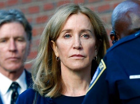 In this Sept. 13, 2019 file photo, actress Felicity Huffman leaves federal court in Boston with her brother Moore Huffman Jr., left, after she was sentenced in a nationwide college admissions bribery scandal. Huffman was sentenced to 14 days in federal prison in Dublin, Calif., but was released early Friday morning, Oct. 25,  after serving 10 days.