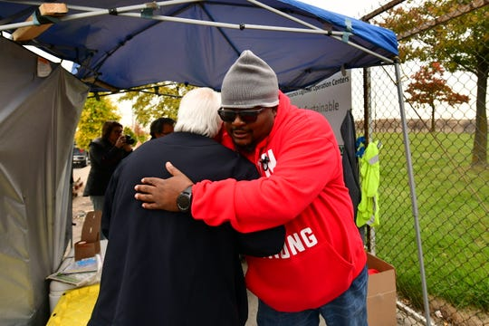 Local 22 workers Nick Wojnarowski, left, and James Reynolds hug each other goodbye at the Detroit-Hamtramck assembly plant in Detroit during the final minutes of the strike, October 25, 2019.