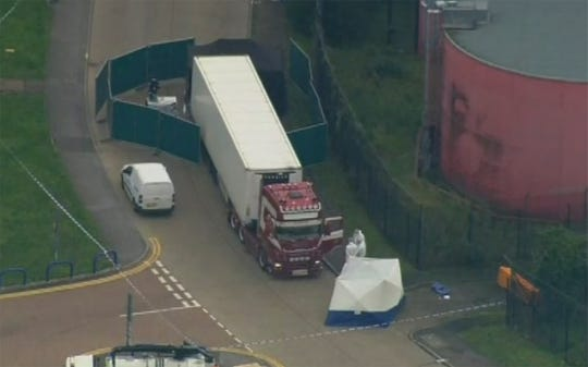 Police forensic officers attend the scene after a truck was found to contain a large number of dead bodies in Thurrock, South England.