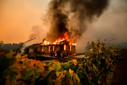 Vines surround a burning building as the Kincade Fire burns through the Jimtown community of unincorporated Sonoma County, Calif., on Thursday, Oct. 24, 2019.
