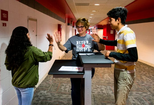 Harrison High School ESL teacher Janelle Nisly, middle, high fives Freshman  Briana Gonzalez Aguilar, left, and Luis Vasquez Martinez, right, both from Mexico, during an early morning English as a New Language class Friday, Oct. 25, 2019.