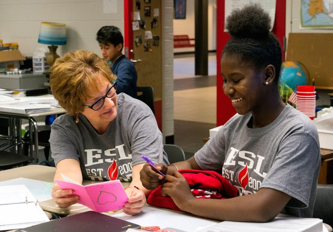 Harrison High School ESL teacher Janelle Nisly, left, goes over an assignment with Freshman Christlove Fragilas, right, from Haiti, during an early morning English as a New Language class Friday, Oct. 25, 2019. The assignment is to write stories that they will read to Stockwell Elementary School students.
